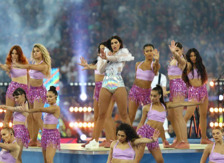 Dua Lipa performing with a group of dancers during the Champions League Final