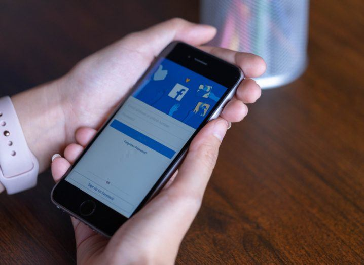 Woman's hands holding a mobile device with the Facebook login screen open.