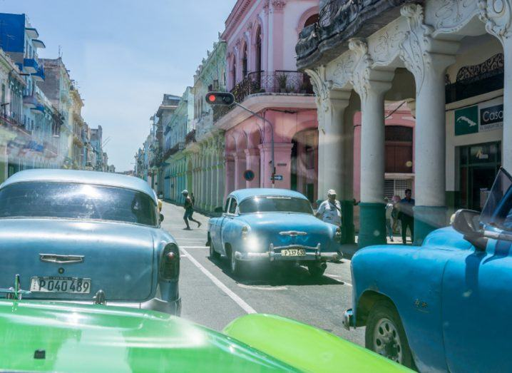 A street in Old Havana, Cuba, with colourful vintage cars parked on both sides.