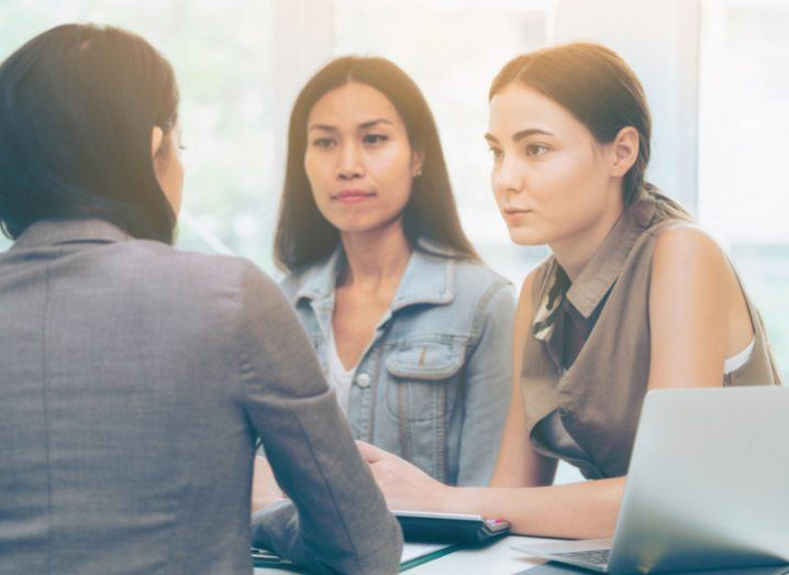 Three women speaking about strategy together at a table during a business meeting.