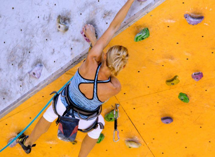A physically fit blonde woman on a purple and yellow climbing wall.