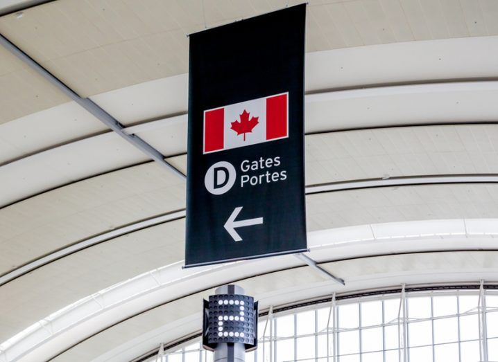An airport sign with the Canadian flag, directing passengers to a boarding gate.