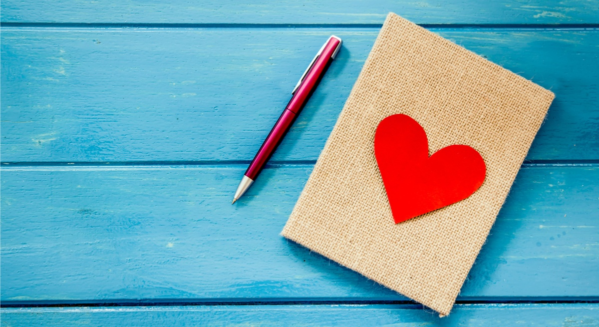 A fabric-covered notebook with a red heart on a blue wooden surface next to a metallic pink pen.