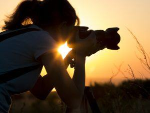 Silhouette of a woman taking a photograph at sunset with a long range lens.