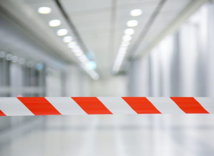 Red and white striped barrier tape blocks a brightly lit white corridor.