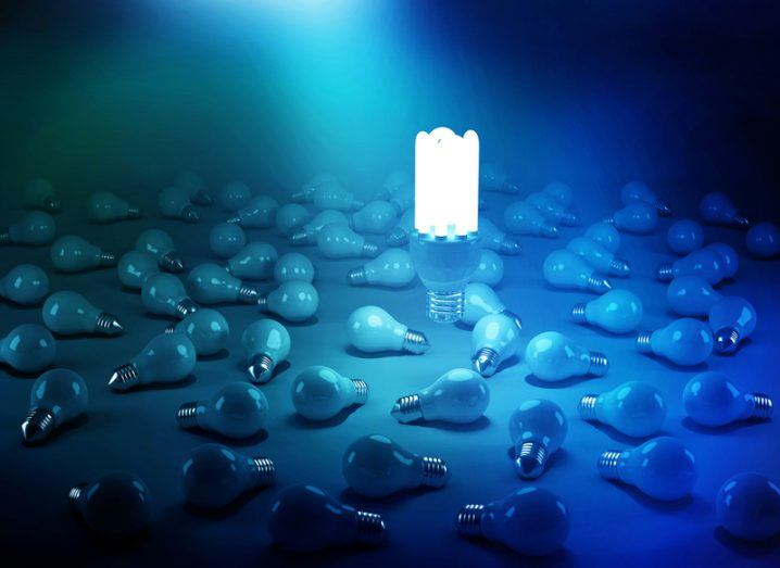 A large glowing lightbulb floats upright amid a blue haze of scattered, unlit small lightbulbs.