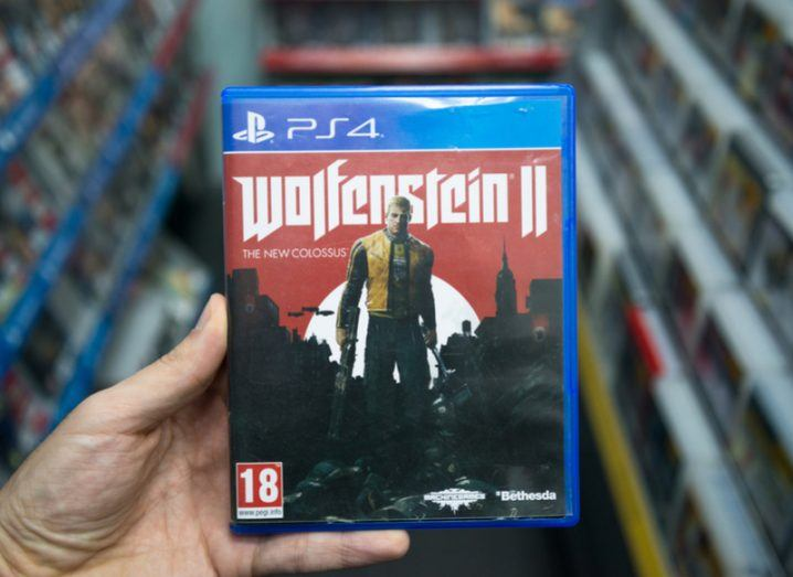 A hand holding the video game 'Wolfenstein 2, The New Colossus'.