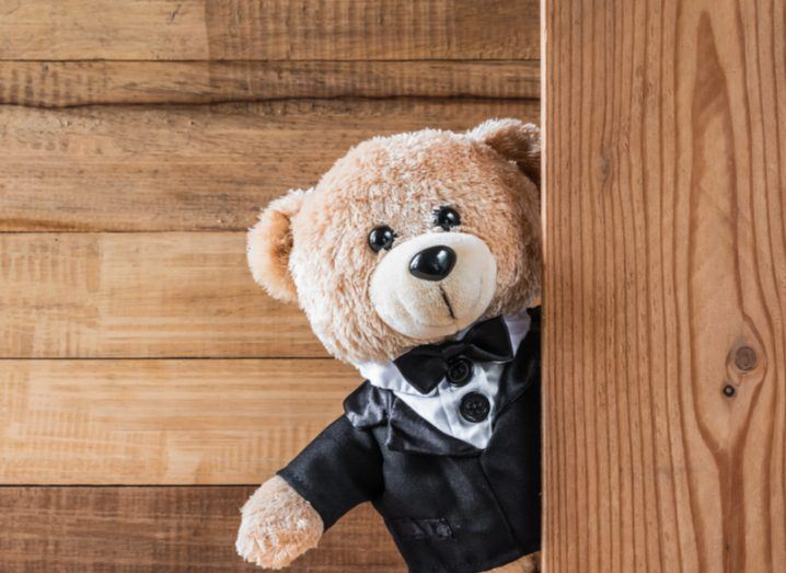 A teddy bear dressed in a fancy black tuxedo with a wooden wall in the background.