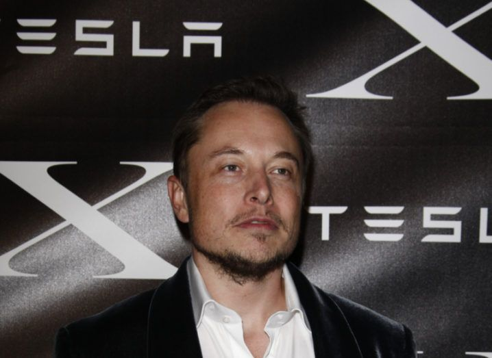 Tesla CEO Elon Musk in a black suit and white shirt at a red carpet event.