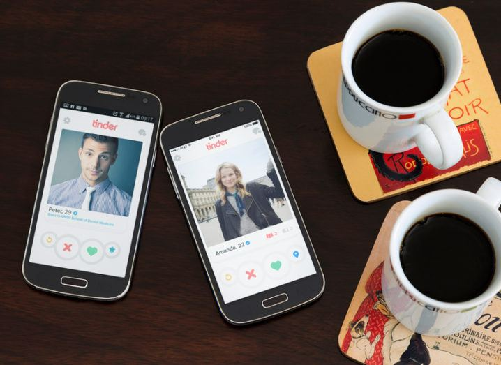 Two smartphones on a table with the Tinder app open.