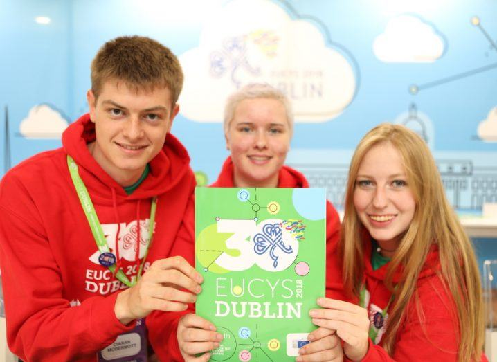 Young blonde students beaming at the camera against a cartoon sky backdrop at EUCYS 2018.