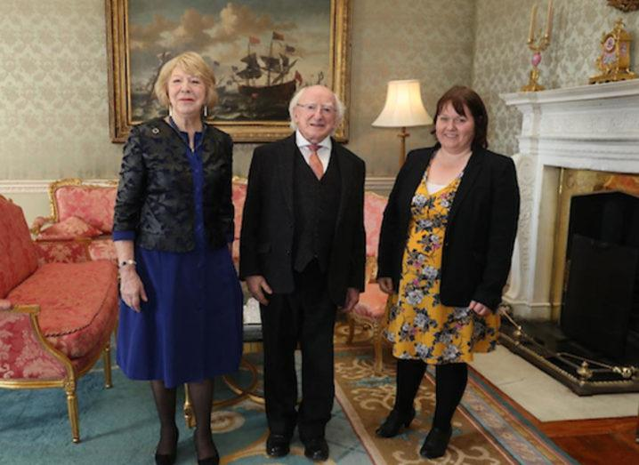 Two women and the President of Ireland in a formal meeting room.