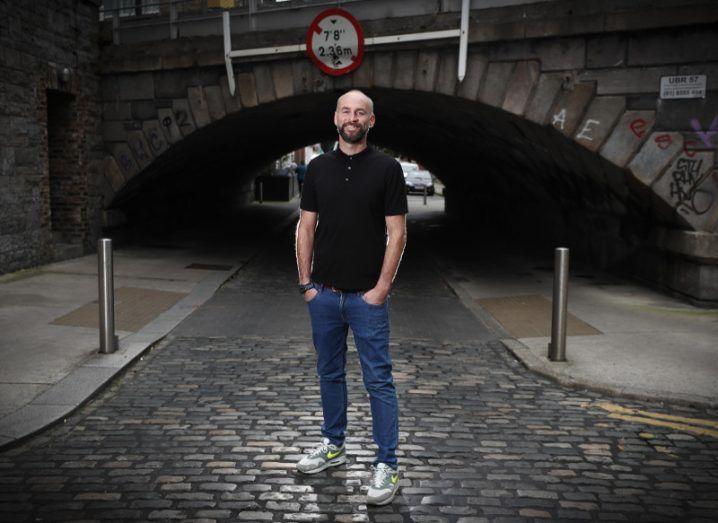 Man in black t-shirt, white runners, standing beside bridge.