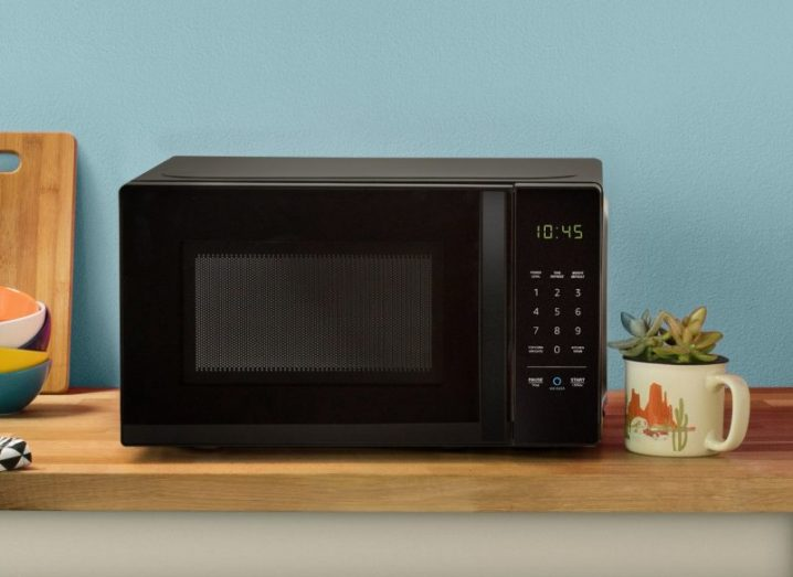 AmazonBasics microwave on a wooden counter in front of a blue wall.