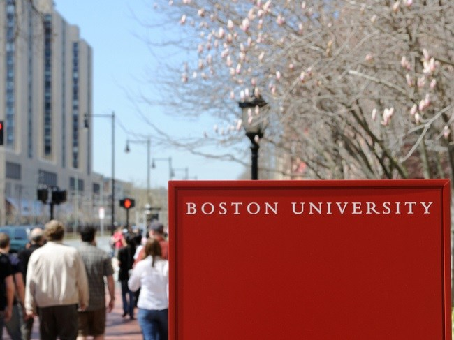 Red Boston University sign with students walking in the background.