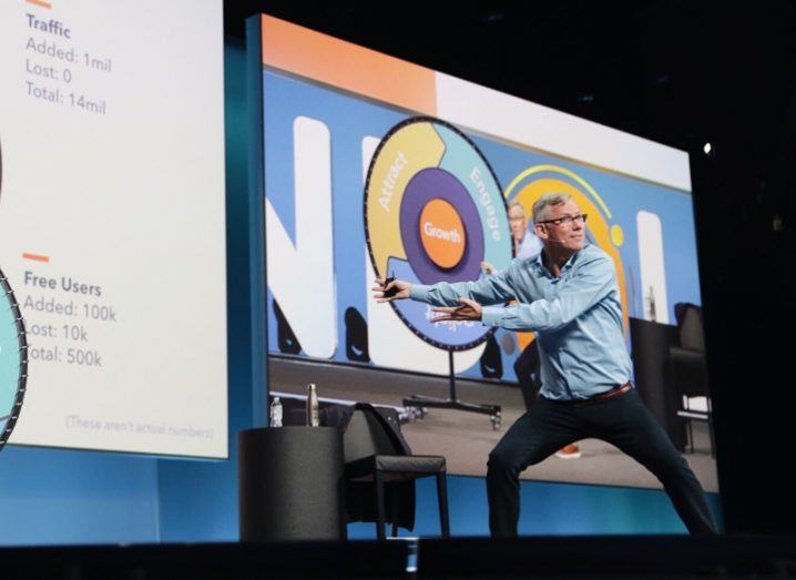 Man standing on a stage pointing to a presentation.
