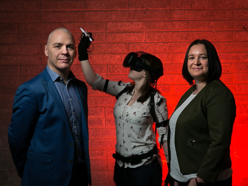 A man and a woman stand beside another woman wearing a VR headset with a red background.