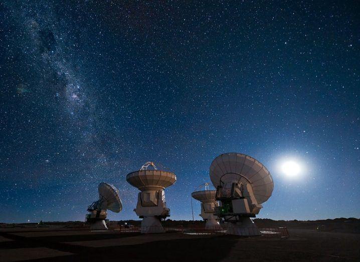 Four antennas of the Atacama Large Millimeter/submillimeter Array (ALMA) gaze up at the star-filled night sky.