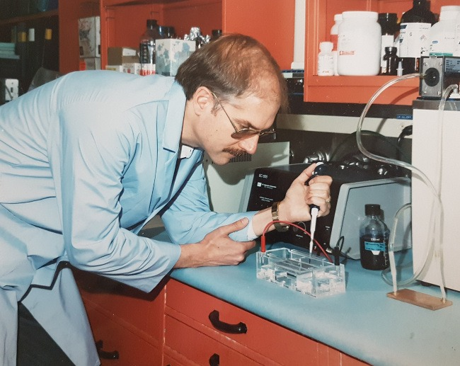 A moustachioed man in a pale blue lab coat pipetting in a lab. The photo appears to have been taken in the 1970s.