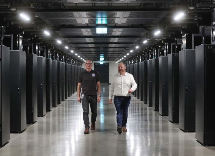 Two men walk between rows of servers in a data centre.