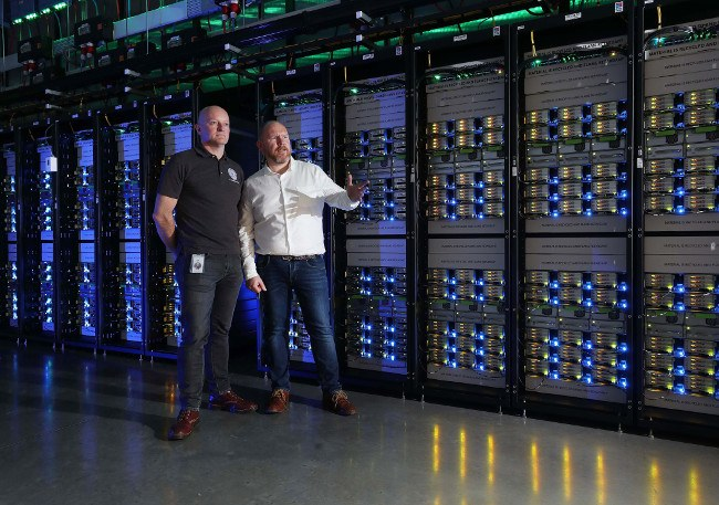 Two men stand beside clusters of servers in Facebook data centre.