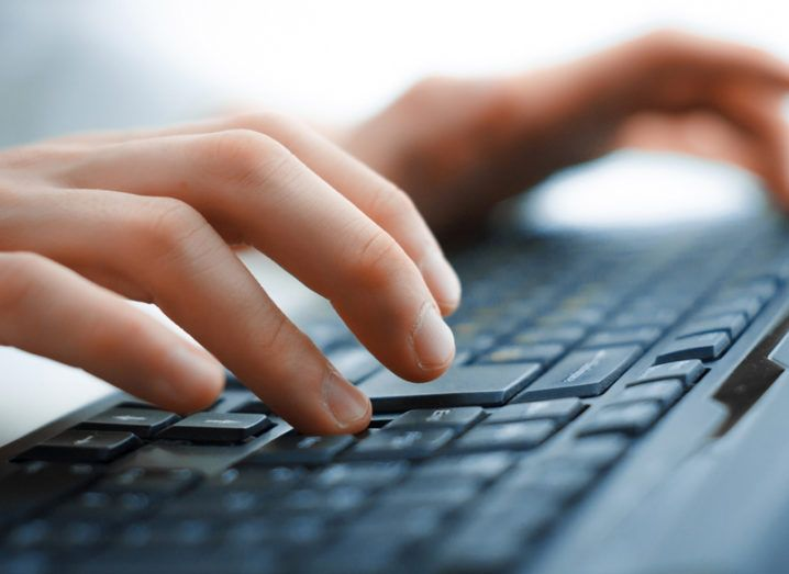 Close-up of a person's hands typing on a black keyboard.