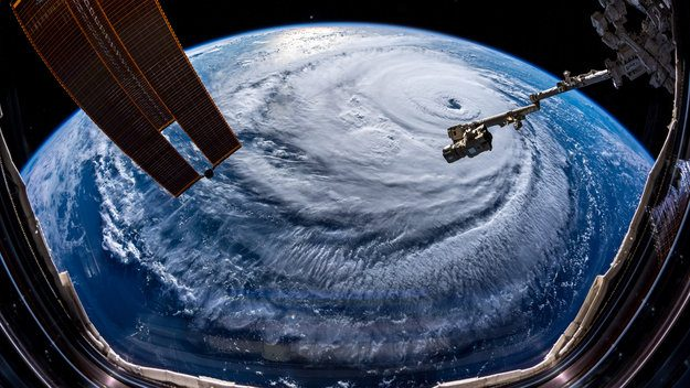 Hurricane Florence, category 2 storm visible from space with satellites in the foreground.