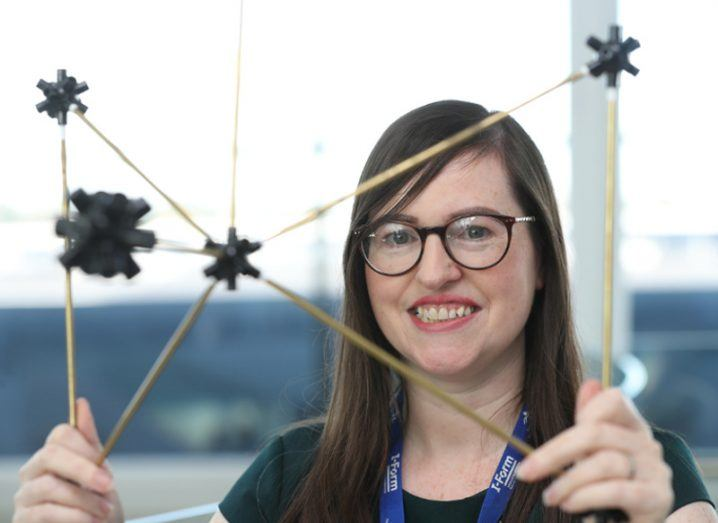 Woman with glasses holding up 3D printed prototype.