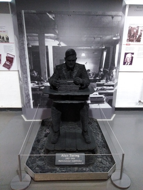 A slate sculpture of a man seated at an Enigma codebreaking machine stands amid a museum exhibition.