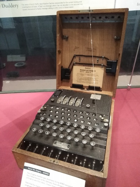 An old machine that looks like a large typewriter in a wooden case is showcased in a museum exhibition.