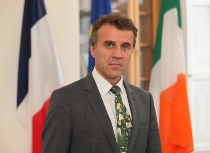 A middle-aged, well-dressed diplomat looking into the camera. He is standing in front of a French flag and an Irish flag.