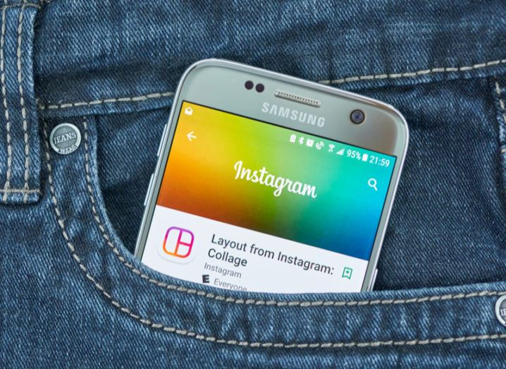 Instagram app on a smartphone sitting in the pocket of a pair of jeans.