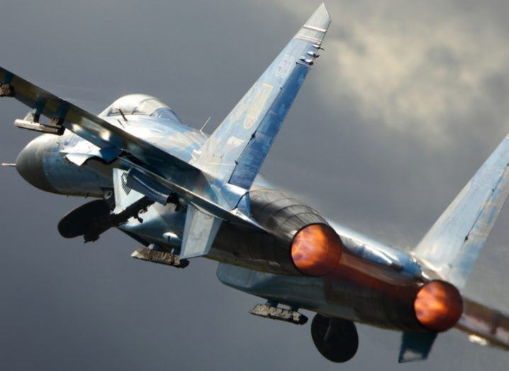 A blue Sukhoi Su-27 taking off with the afterburners on.