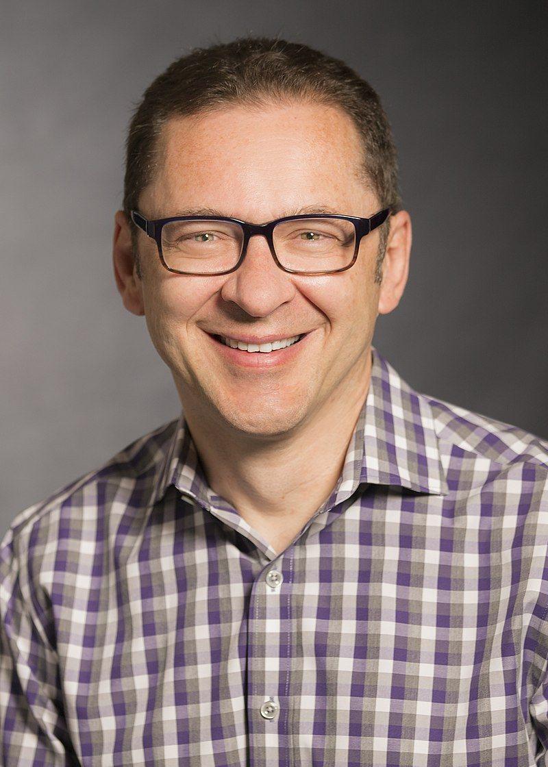 Maciej Kranz smiling, wearing black glasses and a check shirt