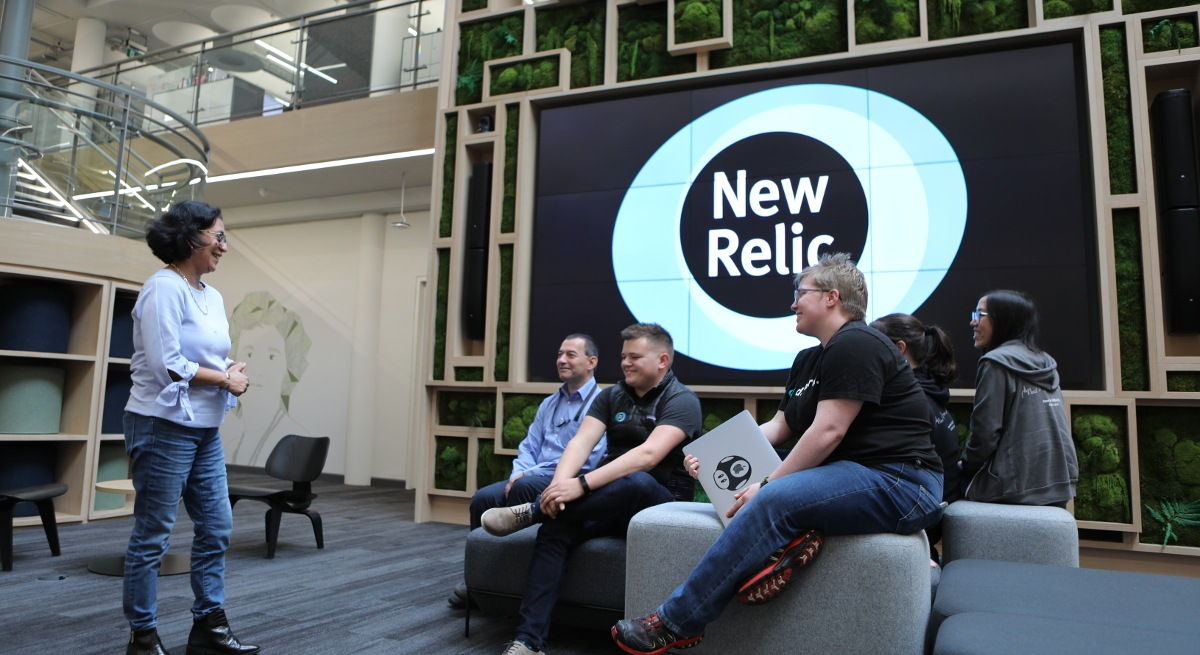 A diverse group of New Relic employees sitting together in the open plan officeon comfy stools facing one standing employee.