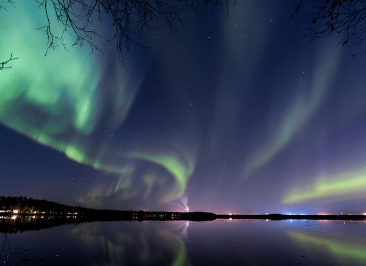 Northern lights over the Finnish city of Finland beside a lake.