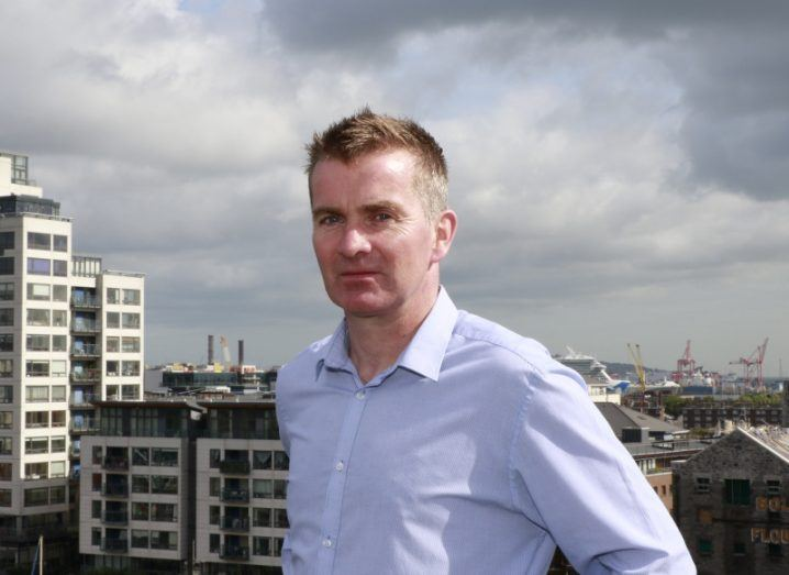 A man in a light blue shirt is photographed on a rooftop with the buildings of Dublin's docklands in the background.
