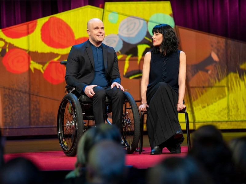 A bald man in a wheelchair speaks to an audience from a colourful stage, while a dark-haired woman seated next to him looks on.