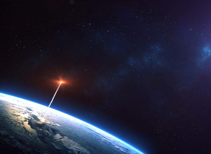 Distant shot of a rocket launching into orbit carrying a satellite on board.
