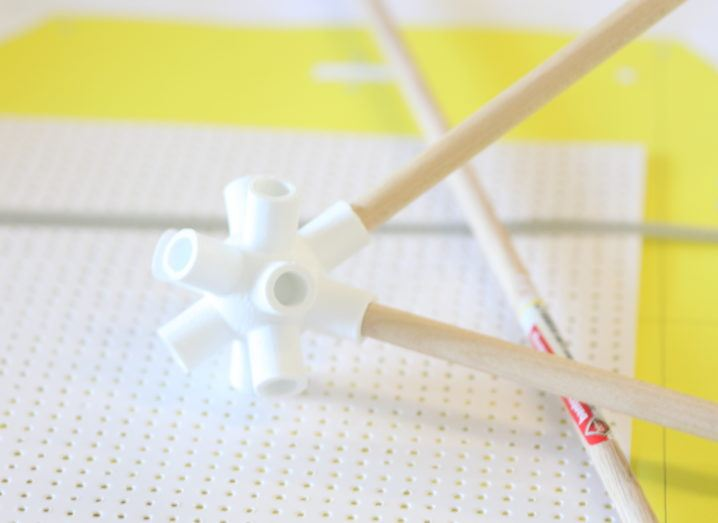 white plastic connector holding two wooden sticks balanced on white dotted paper on bright yellow surface.