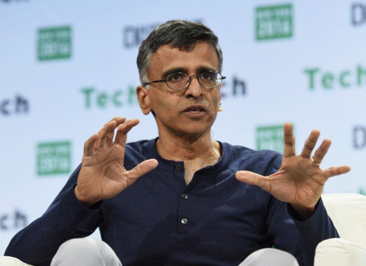 Man in glasses in navy jumper gesturing with his hands in reply to a question at a tech conference.