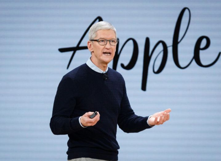 Man in navy jumper presenting on stage in front of blu background with Apple in cursive writing.