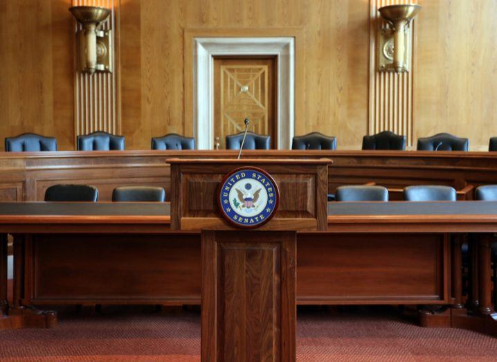 Empty committee hearing room with dark wood podium and black leather seats.