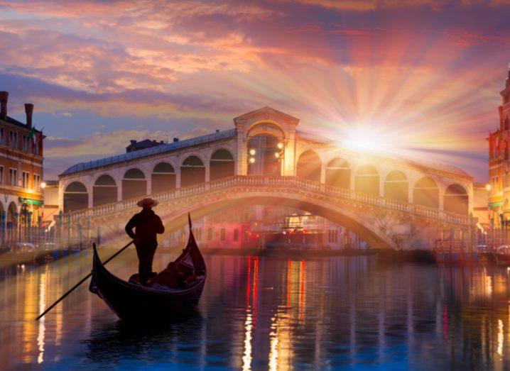 A gondola goes under a bridge in Venice as the sun sets.