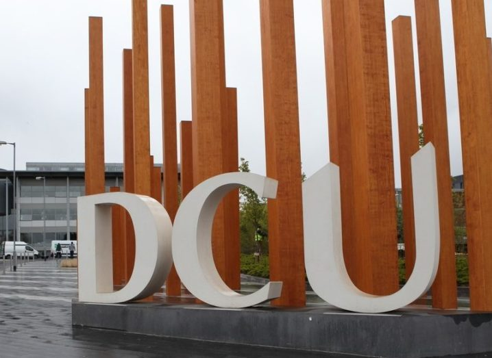 DCU campus featuring a sculpture of the letters 'DCU' with yellow poles behind it.