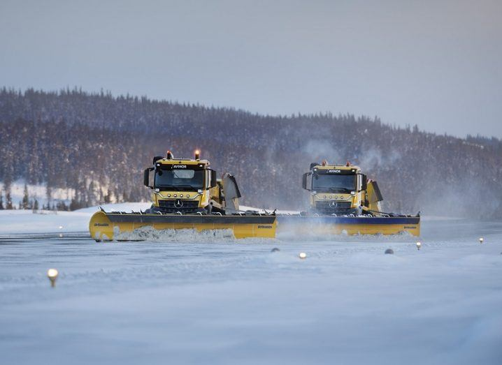 Two of the autonomous Yeti snowploughs clearing snow on a runway.