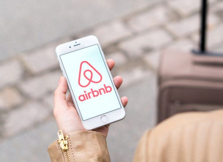 Woman with suitcase holds a smartphone with Airbnb app on the screen.