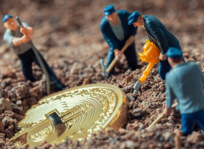 toy figures representing miners dig a cryptocurrency coin out of the sand.