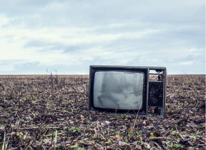 A broken TV in an autumn field.