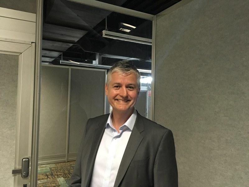 Man in grey sports jacket smiling at camera.